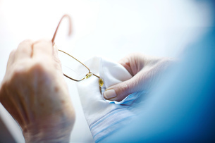 Senior woman cleaning eyeglasses with cloth, mid sectionの写真素材 [FYI03603115]