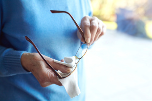 Senior woman cleaning eyeglasses with cloth, mid sectionの写真素材 [FYI03603117]