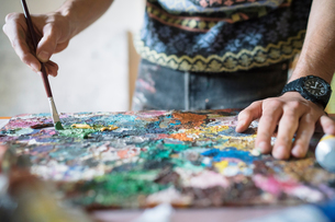 Male artist mixing oil paint on palette in artists studio, close up of handsの写真素材 [FYI03603199]