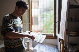 Male artist applying oil paint to palette in artists studioの写真素材 [FYI03603202]
