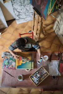 Male artist looking at smartphone while painting canvas in artists studio, overhead viewの写真素材 [FYI03603203]
