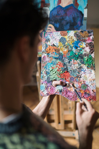 Over shoulder view of male artist mixing oil paint on palette in artists studioの写真素材 [FYI03603207]