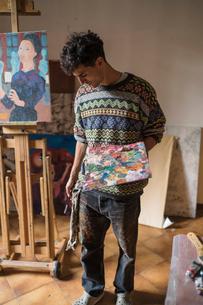 Male artist holding palette in artists studioの写真素材 [FYI03603208]