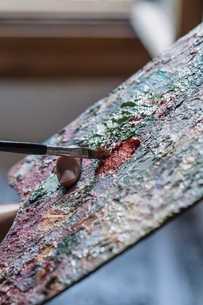 Male artist mixing oil paint on palette, close upの写真素材 [FYI03603218]
