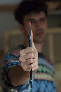 Male artist holding paintbrush in artists studio, close upの写真素材 [FYI03603220]