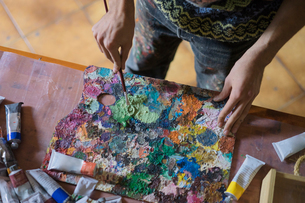 Male artist mixing oil paint on palette in artists studio, mid sectionの写真素材 [FYI03603222]