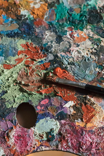 Detail of messy artist palette and paintbrush in artists studio, close upの写真素材 [FYI03603224]