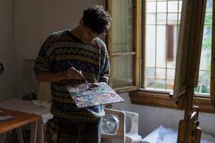 Male artist mixing oil paint on palette in artists studioの写真素材 [FYI03603232]