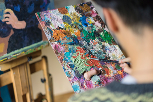 Male artist mixing oil paint on palette in artists studio, over shoulder viewの写真素材 [FYI03603235]