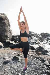 Young woman practicing yoga standing tree pose on beach, Las Palmas, Canary Islands, Spainの写真素材 [FYI03603310]