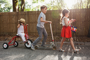 Three children in mini parade, banging drum, riding tricycle and using scooterの写真素材 [FYI03603477]