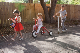 Three children in mini parade, banging drum, riding tricycle and using scooterの写真素材 [FYI03603479]