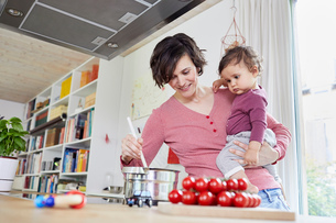 Mother holding baby girl in kitchen, whilst stirring pot on stoveの写真素材 [FYI03603500]