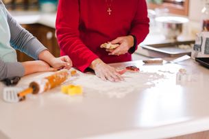 Girl and grandmother preparing flour on kitchen bench, mid sectionの写真素材 [FYI03603718]