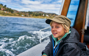 Boy looking out from motor boat at sea, Puno, Peruの写真素材 [FYI03603726]