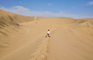Boy with sandboard looking out over sand dunes, Ica, Peruの写真素材 [FYI03603763]