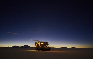 Recreational vehicle, travelling at dusk, across salt flats, Salar de Uyuni, Uyuni, Oruro, Bolivia,の写真素材 [FYI03603769]