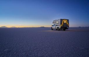 Recreational vehicle, travelling at dusk, across salt flats, Salar de Uyuni, Uyuni, Oruro, Bolivia,の写真素材 [FYI03603772]