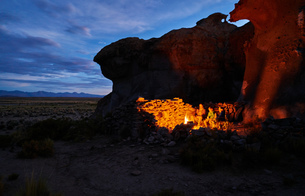 Mother and sons, sitting beside camp fire at dusk, Oruro, Oruro, Bolivia, South Americaの写真素材 [FYI03603831]