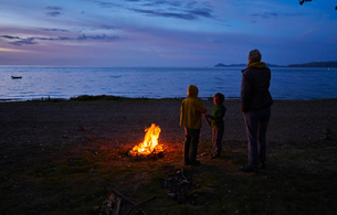 Mother and sons beside camp fire, looking at lake view, rear view, Copacabana, Oruro, Bolivia, Southの写真素材 [FYI03603864]
