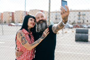 Mature hipster couple taking selfie by wire fenceの写真素材 [FYI03603977]