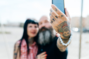 Mature tattooed hipster couple taking selfie, close up of handの写真素材 [FYI03603980]