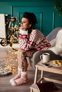 Young woman sitting at home, wearing christmas jumper, thoughtful expressionの写真素材 [FYI03604218]