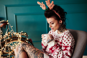 Young woman sitting at home, wearing christmas jumper and antlers, drinking hot drinkの写真素材 [FYI03604220]