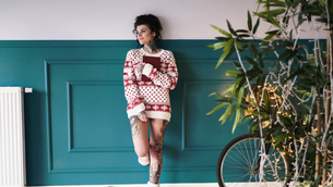 Young woman at home, leaning against wall, wearing christmas jumper, thoughtful expressionの写真素材 [FYI03604222]