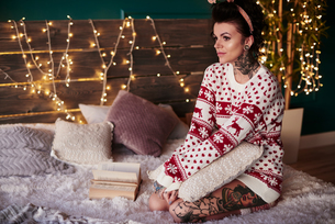 Young woman sitting on bed, wearing christmas jumper, thoughtful expressionの写真素材 [FYI03604223]