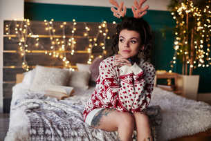 Young woman sitting on edge of bed, wearing christmas jumper and antlers, thoughtful expressionの写真素材 [FYI03604224]