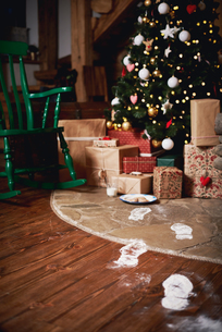 Christmas tree surrounded by presents, Santa's footprints leading towards treeの写真素材 [FYI03604255]