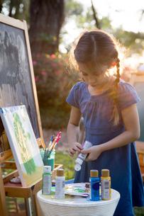 Girl squeezing paint onto palette in gardenの写真素材 [FYI03604292]