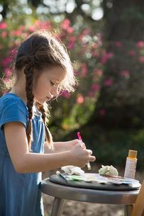 Girl preparing paint palette in gardenの写真素材 [FYI03604293]