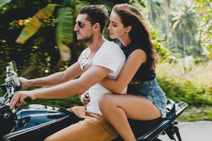 Young couple riding on motorcycle on rural road, Krabi, Thailandの写真素材 [FYI03604471]
