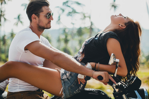 Young woman astride boyfriend on motorcycle, Krabi, Thailandの写真素材 [FYI03604472]