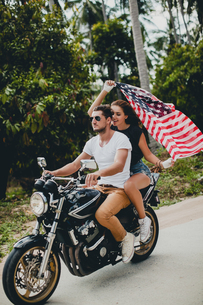 Young couple holding up American flag while riding motorcycle on rural road, Krabi, Thailandの写真素材 [FYI03604474]