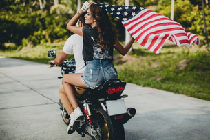 Young couple holding up American flag while riding motorcycle on rural road, Krabi, Thailand, rear vの写真素材 [FYI03604475]