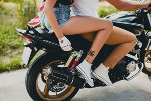 Young couple riding motorcycle on rural road, Krabi, Thailand, waist downの写真素材 [FYI03604476]
