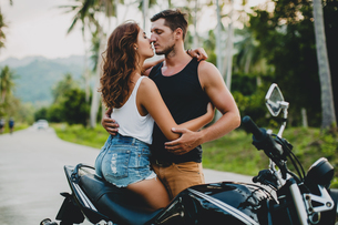 Romantic young couple embracing by motorcycle on rural road, Krabi, Thailandの写真素材 [FYI03604478]