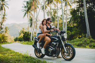 Young couple riding on motorcycle on rural road, Krabi, Thailandの写真素材 [FYI03604480]