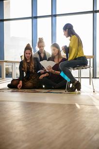 Team of female designers looking at colour swatches on design studio floorの写真素材 [FYI03604482]