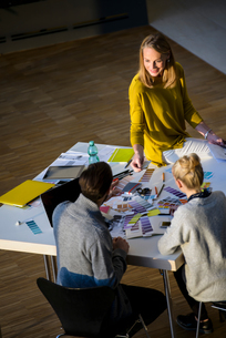 Male and female designers discussing colour swatches on design studio tableの写真素材 [FYI03604483]