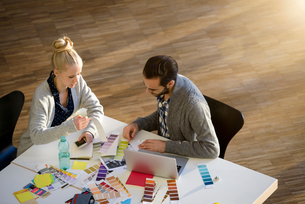 Male and female designer discussing colour swatches on design studio tableの写真素材 [FYI03604485]