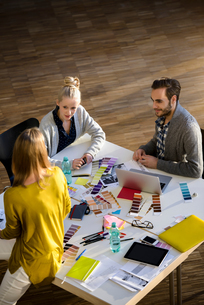 Male and female designers discussing colour swatches on design studio tableの写真素材 [FYI03604486]