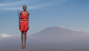 Masai man with traditional dress jumping in front of Mount Kilimanjaro, Amboseli, Rift Valley, Kenyaの写真素材 [FYI03604517]