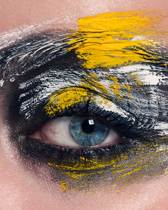 Studio portrait of blue eyed woman with painted face, close up of eyeの写真素材 [FYI03604558]