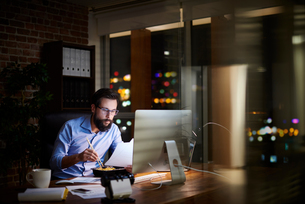 Young businessman reading paperwork and eating takeaway at office desk at nightの写真素材 [FYI03604605]
