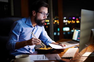 Young businessman looking at computer and eating takeaway at office desk at nightの写真素材 [FYI03604607]