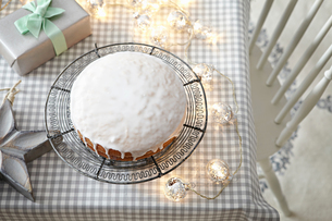 Iced cake on table with decorative lightsの写真素材 [FYI03604670]